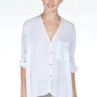 Stay casual and chic with the Ordinary Love Oversize Top. This oversize blouse top features thin soft cotton fabrication, silver button up closure, rollover long sleeve with button closure, asymmetrical bust pocket, asymmetrical bottom hemline, and finishe