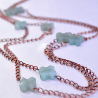 Simple natural wrapped green jade crosses on copper chain.