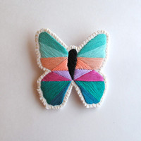 Geometric butterfly brooch hand embroidered with mint and emerald green purples and peach on cream muslin with felt back Spring fashion