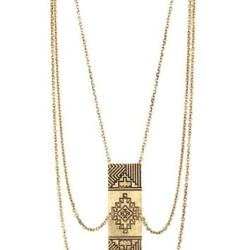Tiered chain necklace featuring a pressed tribal pendant with gemstone accents.