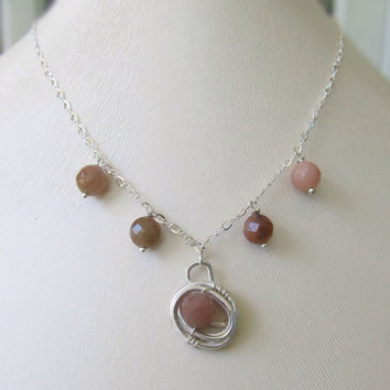 Dainty silver and natural stone unique necklace adorned with a silver nest and dangling natural stones. Handmade jewelry.