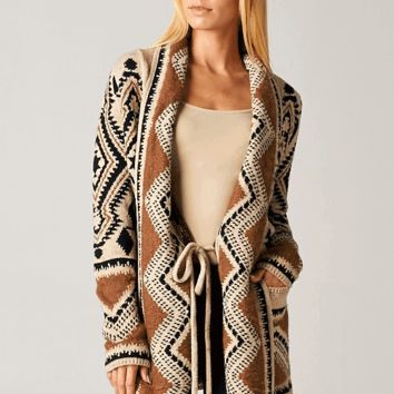 Featuring thick woven knit, ethnic print throughout, open front with self-tie at waist closure, double lapels, long sleeves, longline construction, and finished with two side pockets. Unlined. Pair with leggings and ankle booties.