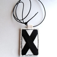 Double sided necklace hand embroidered X O in black on cream muslin hanging from black leather cord hugs and kisses