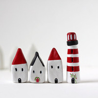 Three little clay houses and a striped lighthouse - white, black and red