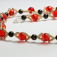 Red and black necklace with golden colored elements