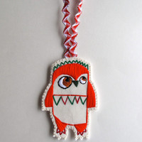 Owl ornament hand embroidered geometric shapes in bright Christmas reds and greens on cream muslin and cream felt with holiday ribbon loop