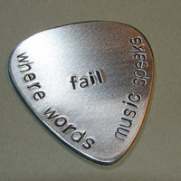 Stamped aluminum guitar pick where words fail music speaks