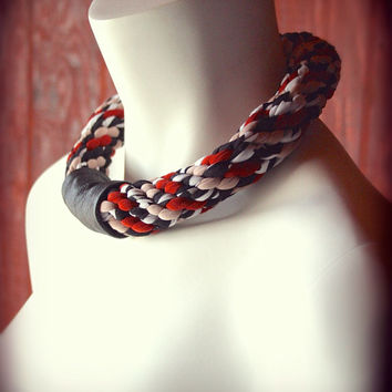 chunky jersey necklace braided with strips of black, white, and red fabric and features a black leather band - ready made by Needless Studio