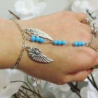 "Angel Wing ""Slave Bracelet"" Ring with baby blue beads. The Angel wings have roses on them.  Adjustable. Fits wrists 6 to 8 inches."