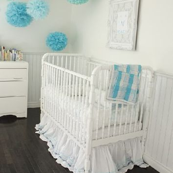 bedrooms - white vintage crib beadboard white baroque frame blue green pom poms espresso stained wood floors inthefunlane.com Adorable nursery