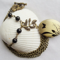 Round locket with butterfly on front cover adorned withblack glass beads and bronze accents