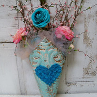 Recycled ceiling tile wall pocket painted in a robins egg blue filled with pink and aqua florals Anita Spero
