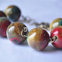 Handpainted ceramic beaded bracelet on antiqued brass wire.