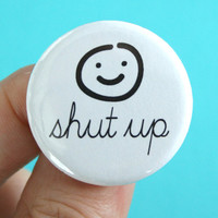 shut up. 1.25 inch button. cursive, smiley face.