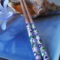 Pair of bamboo chopsticks with polymer clay handles in purple and lime green retro design