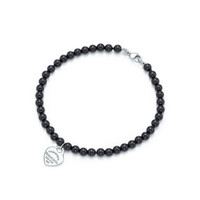 Tiffany & Co. - Return to Tiffany™ mini heart tag in silver on a black onyx bead bracelet.
