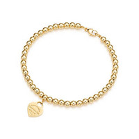 Tiffany & Co. - Return to Tiffany™ mini heart tag in 18k gold on a bead bracelet.